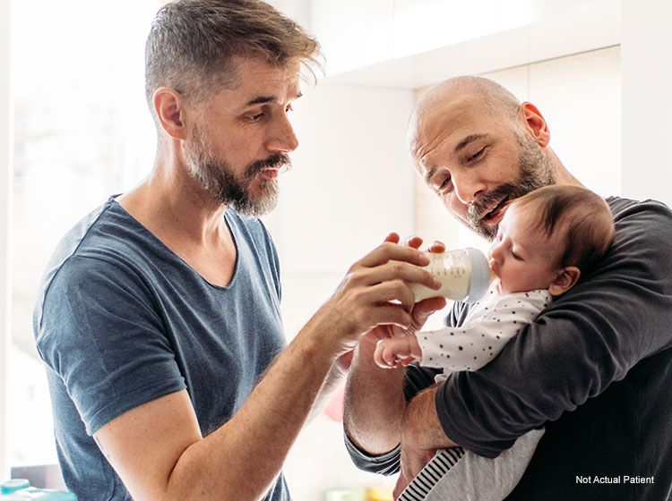 happy homosexual couple with baby